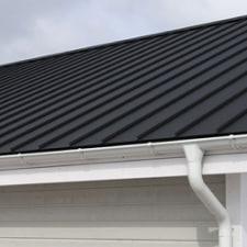 Black metal roof with white gutters