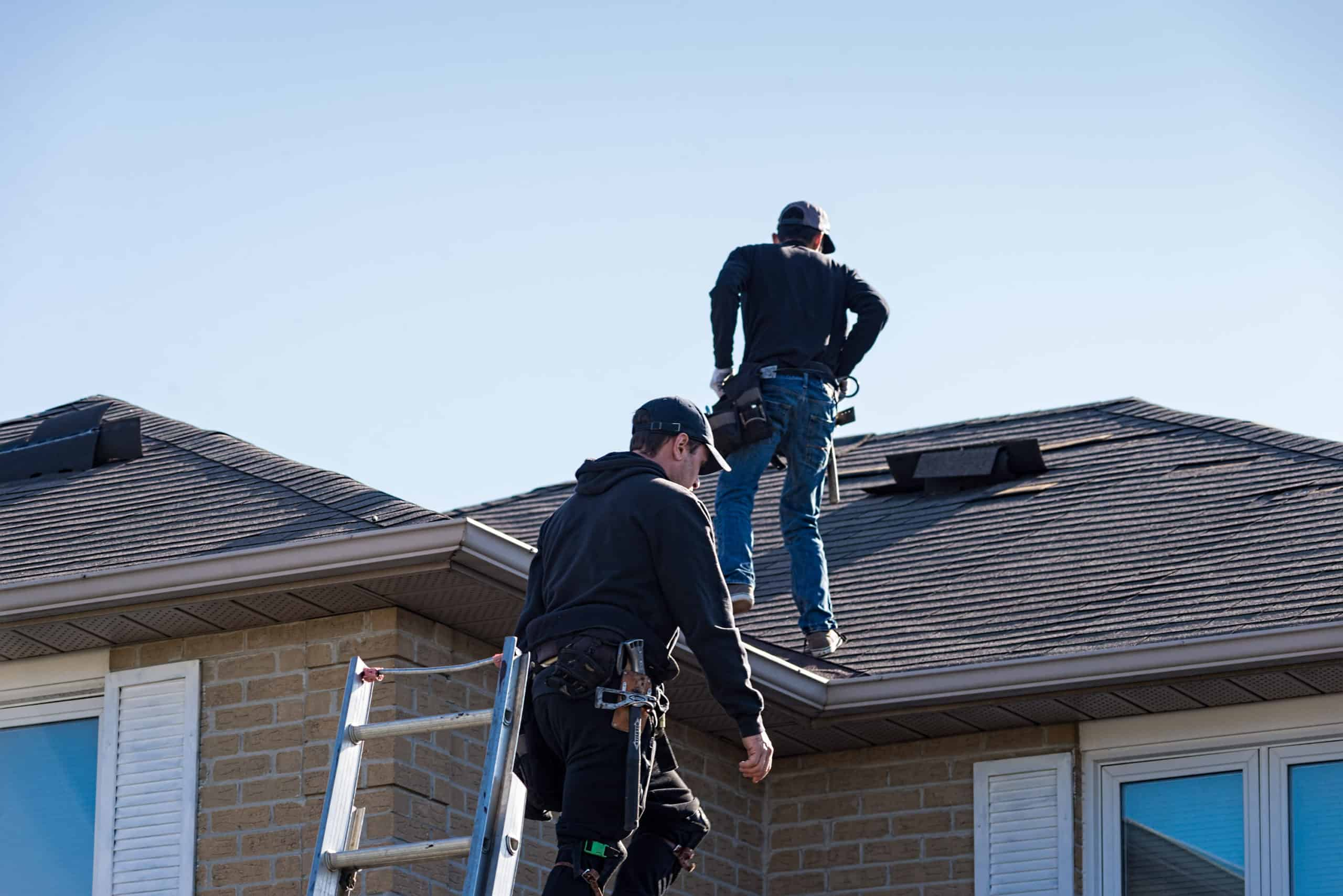 Two mean climbing onto a roof to inspect it