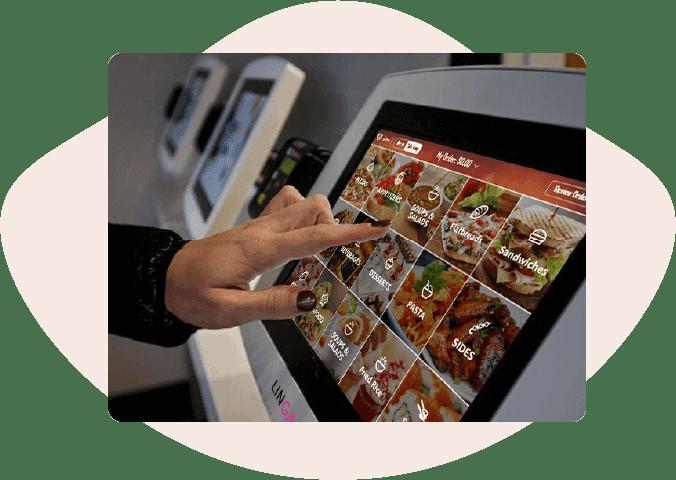 hand touching screen on self-ordering restaurant koisk