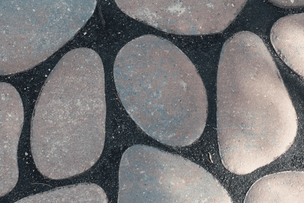 Round organic shaped concrete pavers with black filling between for the Environmental Paver Collection