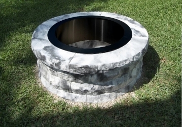 A fire pit built with a metal ring and pavers