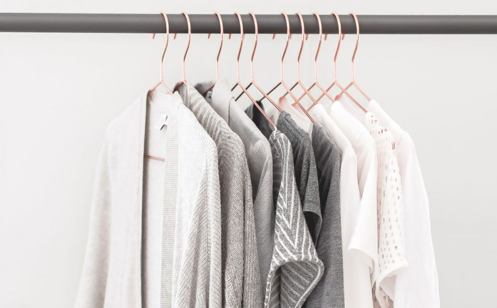 rod with neutral colored women's clothing hanging on rose gold hangers
