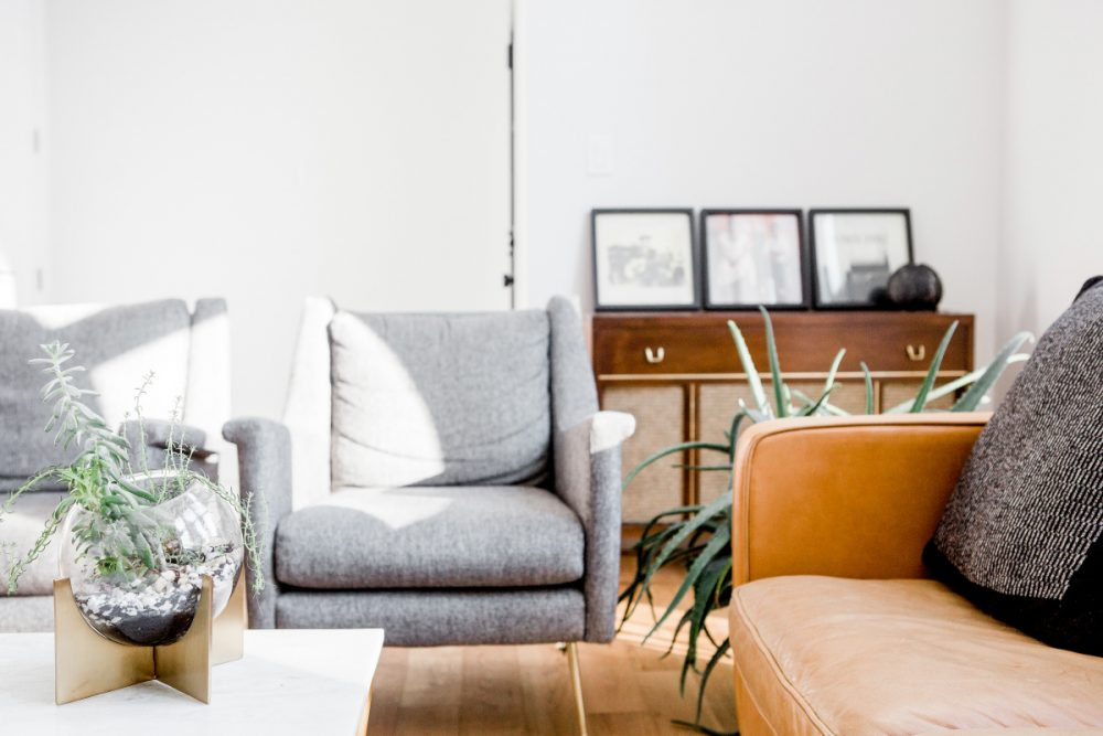 minimalist living room with two small gray accent chairs, coffee table, side table and a few plants