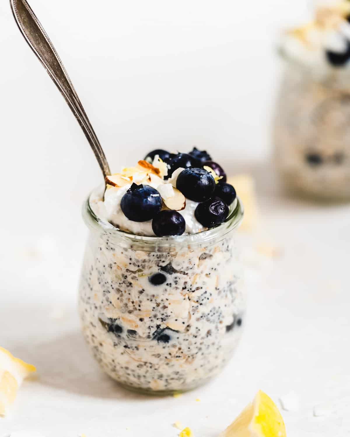 Jar full of oats with blueberries on top and a spoon inside.