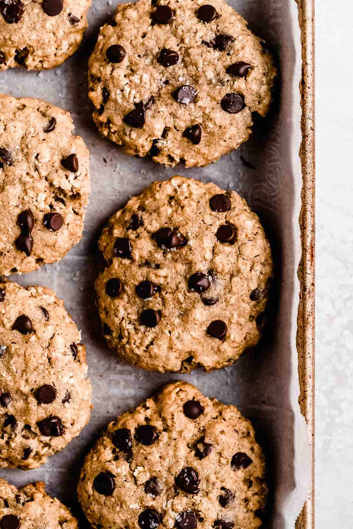 Close up overhead image of freshly baked Oatmeal Chocolate Chip Cookies on a baking sheet.