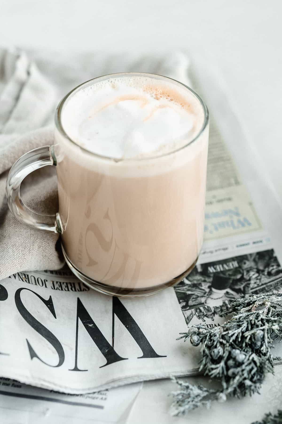 Close up image of a clear mug of Maple Sea Salt Almond Milk Latte sitting on top of a newspaper with a gray linen cloth nearby.