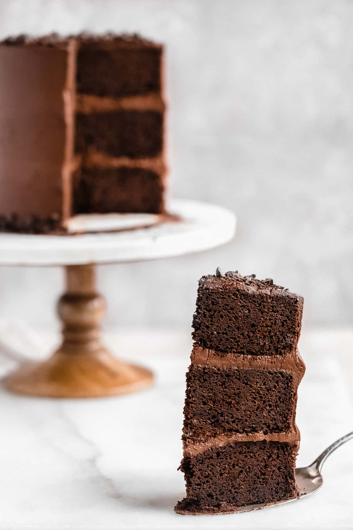 Closeup photo of a single piece of Blackout Chocolate Paleo Cake resting on a silver cake server.  The remaining cake - with this piece removed - can be seen in the background sitting on a white marble cake plate.