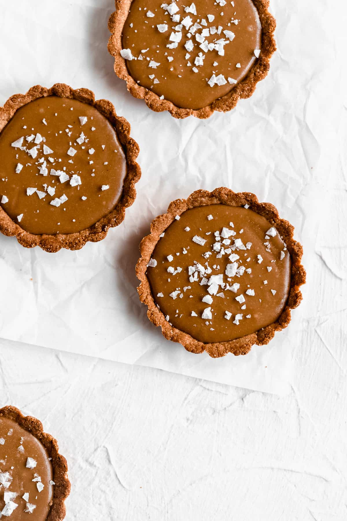 Overhead photo of three Vegan Salted Caramel Tarts arranged on white parchment paper.