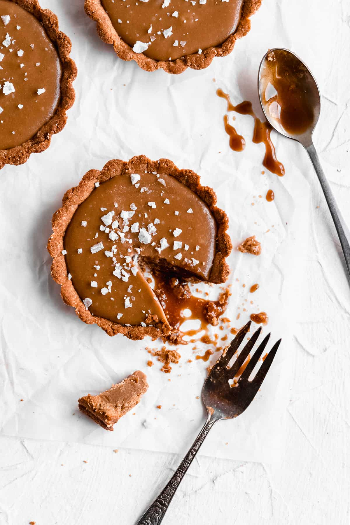 Overhead photo of completed Vegan Salted Caramel Tarts arranged on white parchment paper.  A bite has been taken from one tart and a spoon lays nearby with caramel sauce on it.