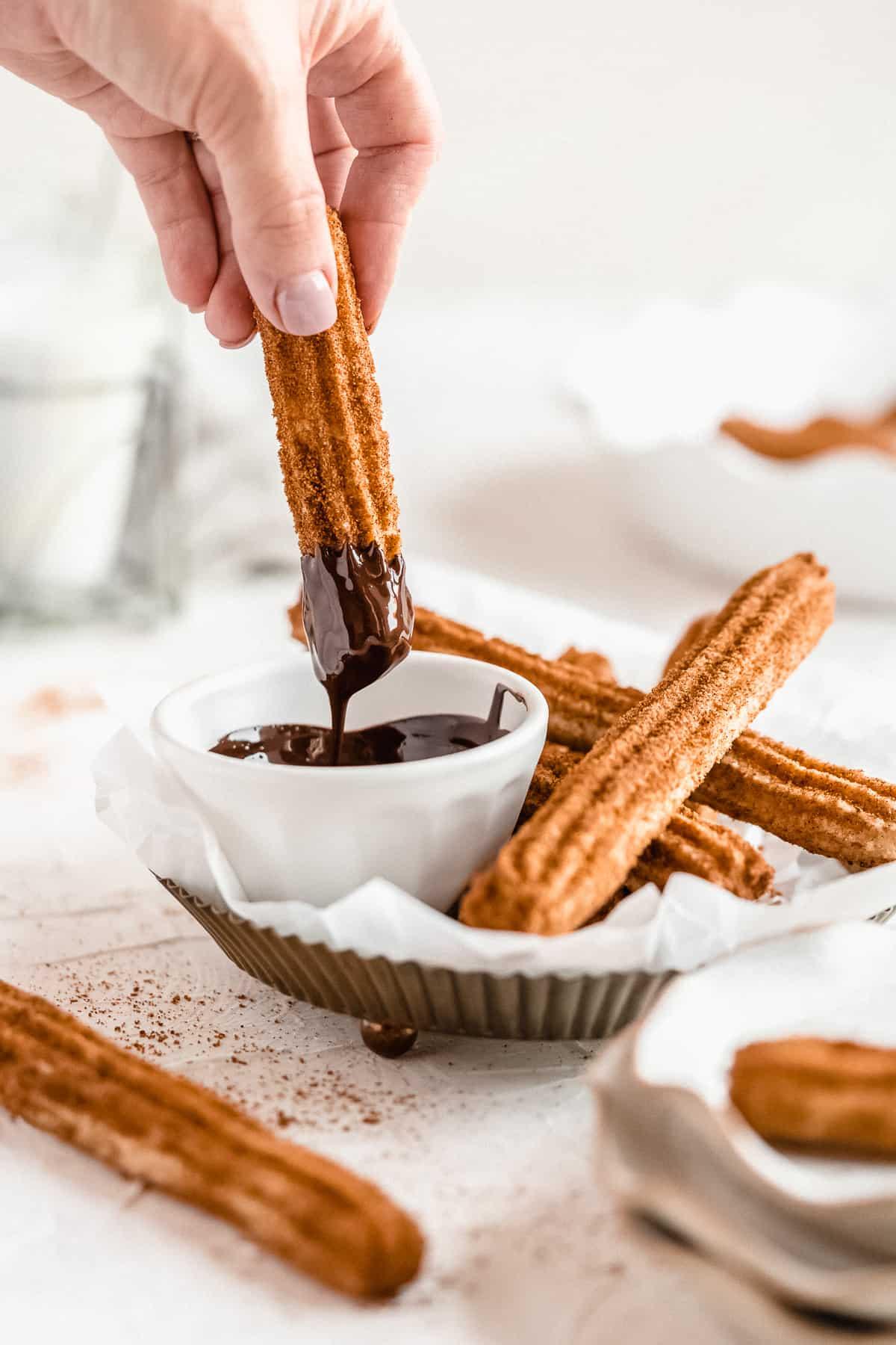 Hand dipping vegan churro into chocolate.