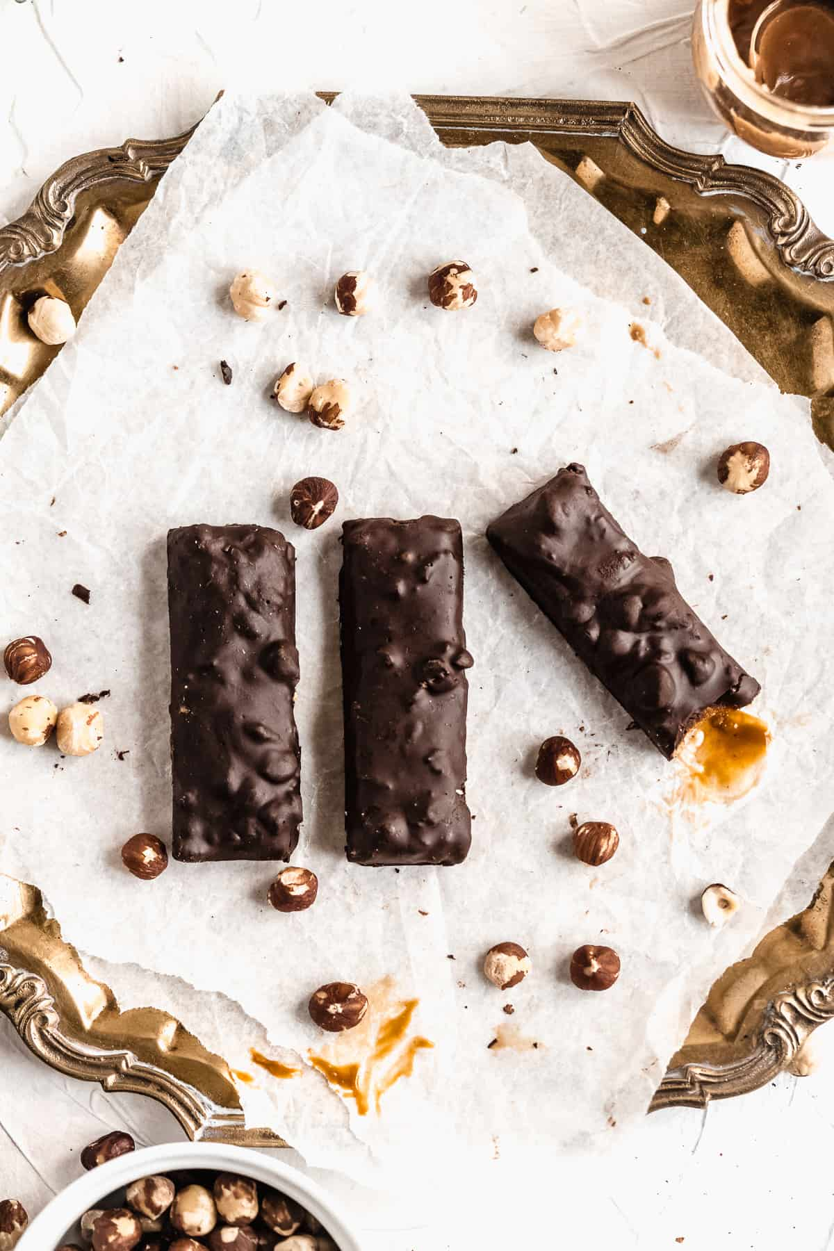 Overhead photo of three Vegan Hazelnut Snicker Bars sitting on white parchment paper on a vintage silver tray.  A bite is taken out of one bar to show the gooey inside.  Additional hazelnuts are sprinkled around.