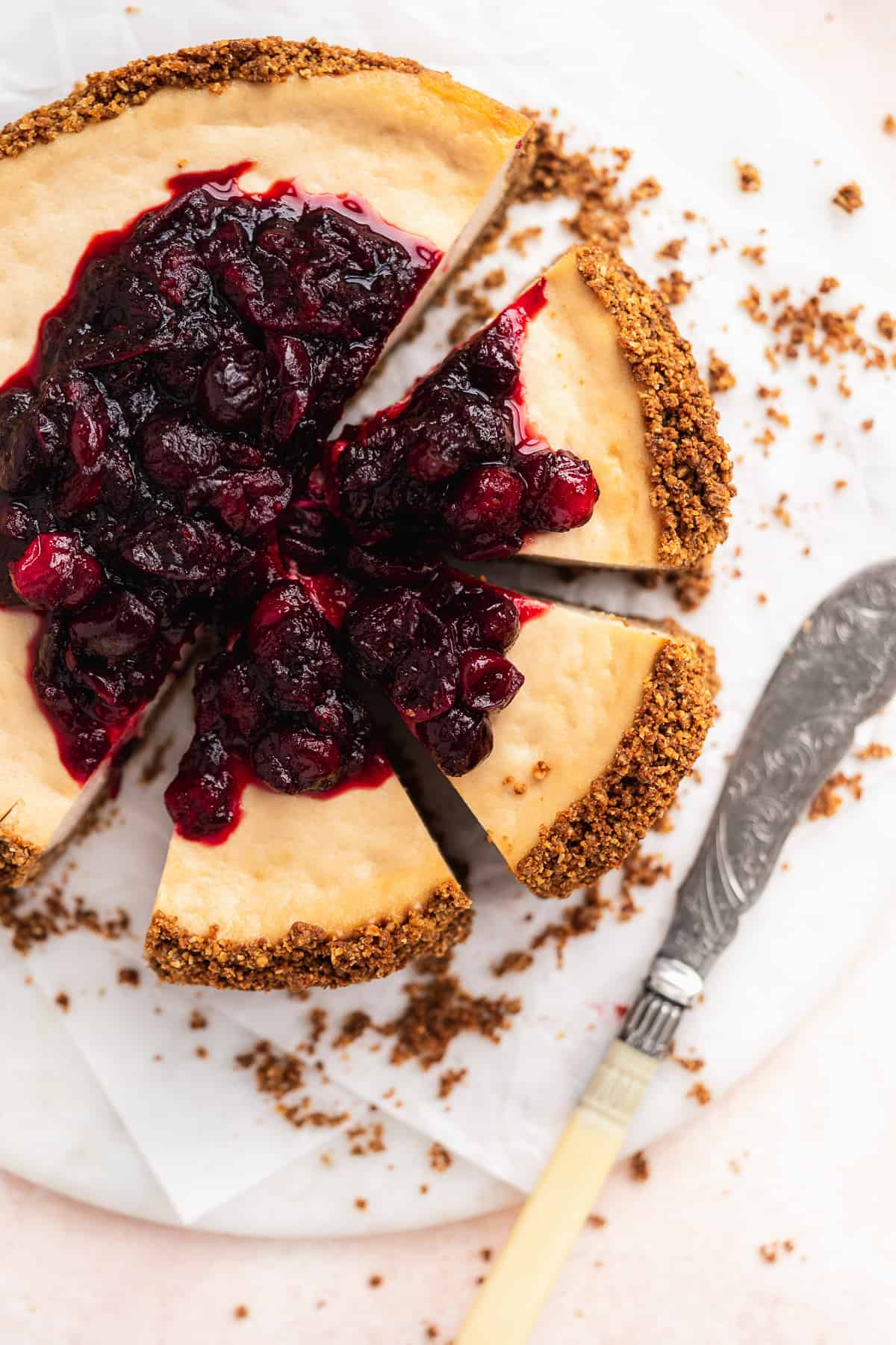 Overhead photo of the Vegan Baked Cranberry Cheesecake with Graham Cracker Crust with 3 slices cut and separated from the whole cake.  Silver pearl handled knife lays nearby.