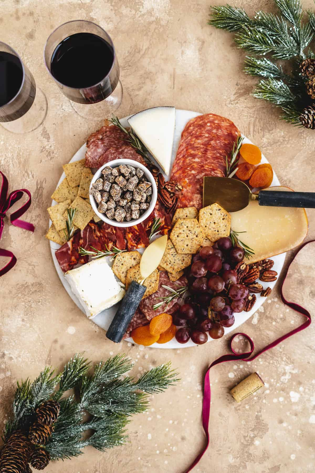 Overhead photo of round white marble slab covered with grapes, pecans, dried fruits, and assorted meats and cheeses.  Two glasses of red wine and gold cheese knives sit nearby.