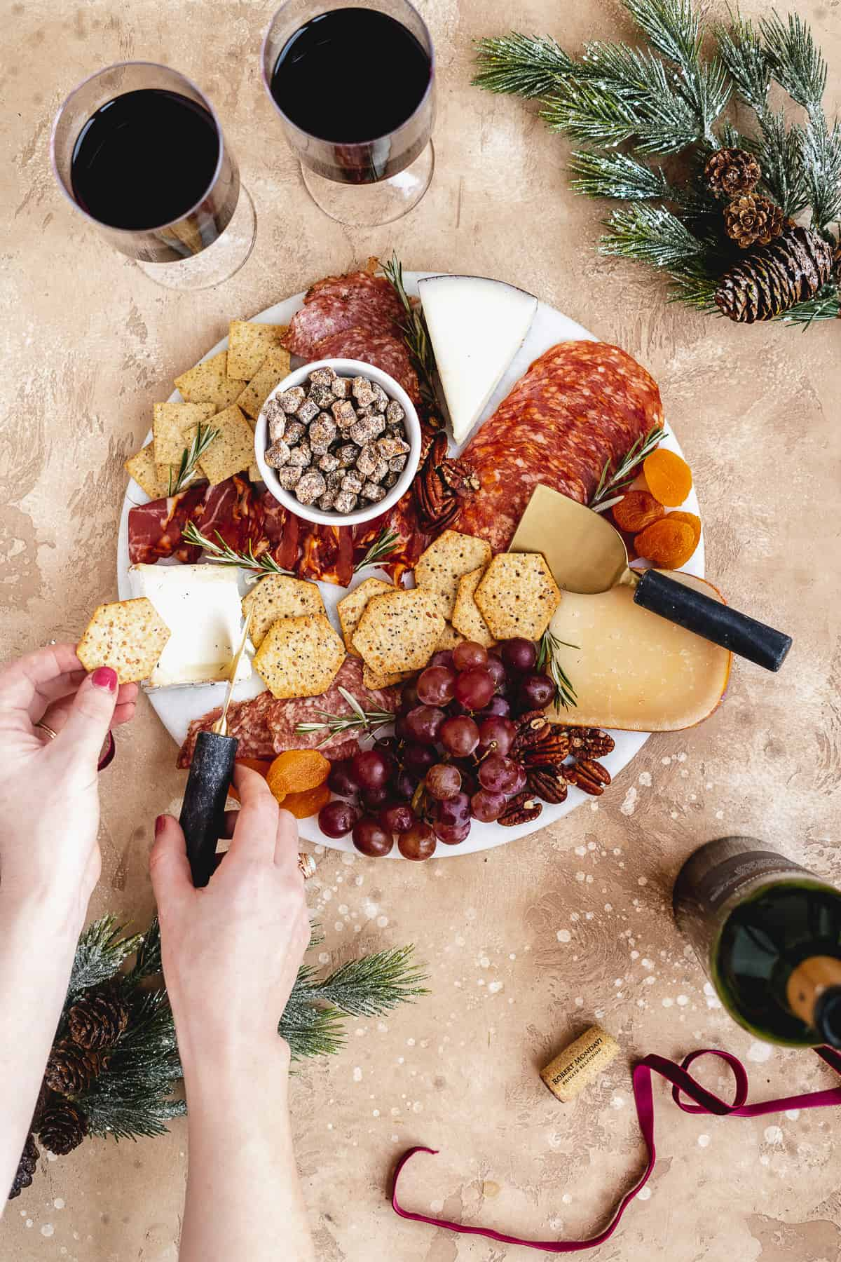 Overhead photo of round white marble slab filled with assorted meats, cheeses, nuts and fruits.  Two hands are holding a cracker and cutting some cheese to place on the cracker.
