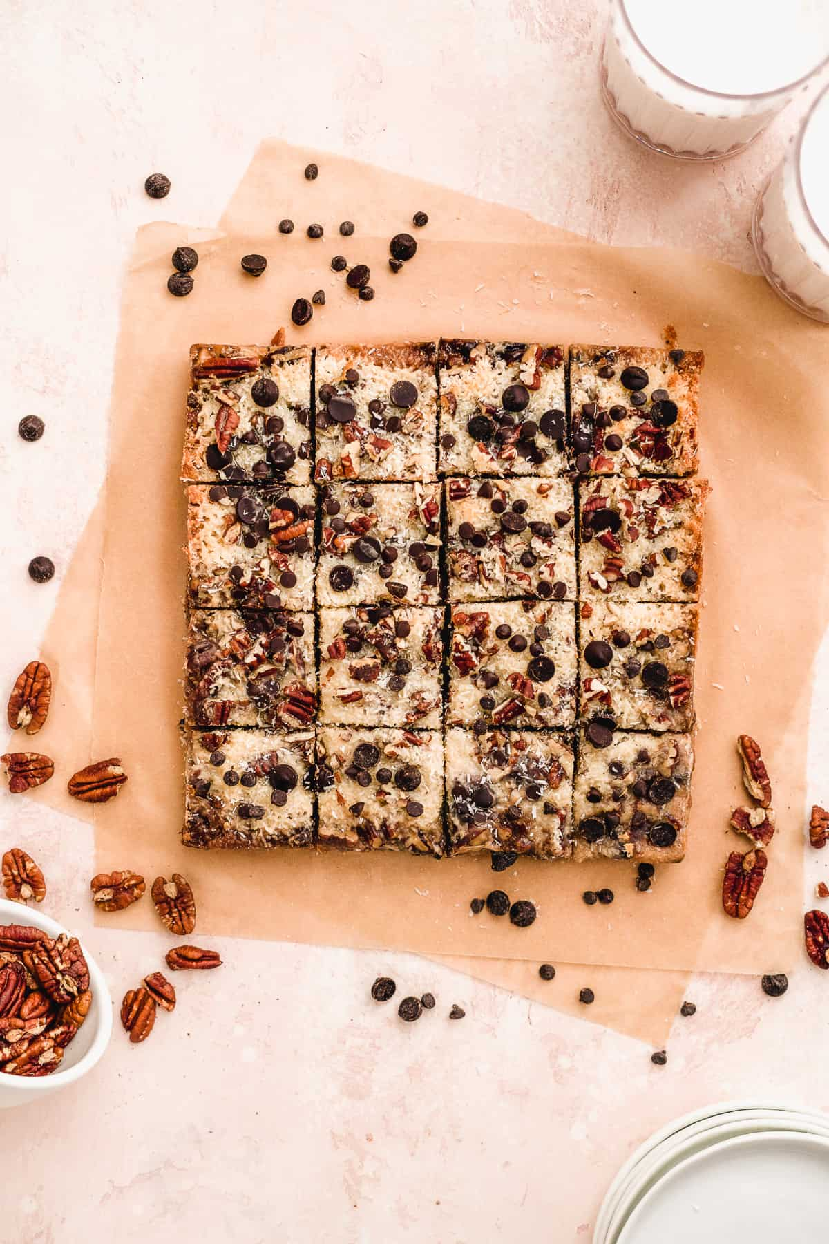 Overhead view of baked Toasted Oat Seven Layer Magic Cookie Bars on parchment paper cut into 16 squares and ready to be enjoyed.  Whole pecans and chocolate chips are sprinkled around.