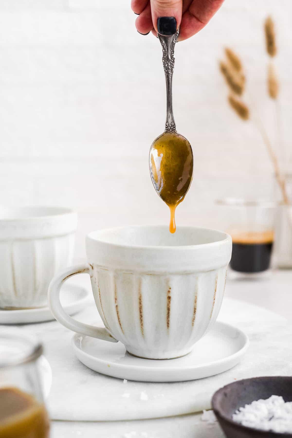 Spoon upside down dripping caramel inside a white coffee mug.
