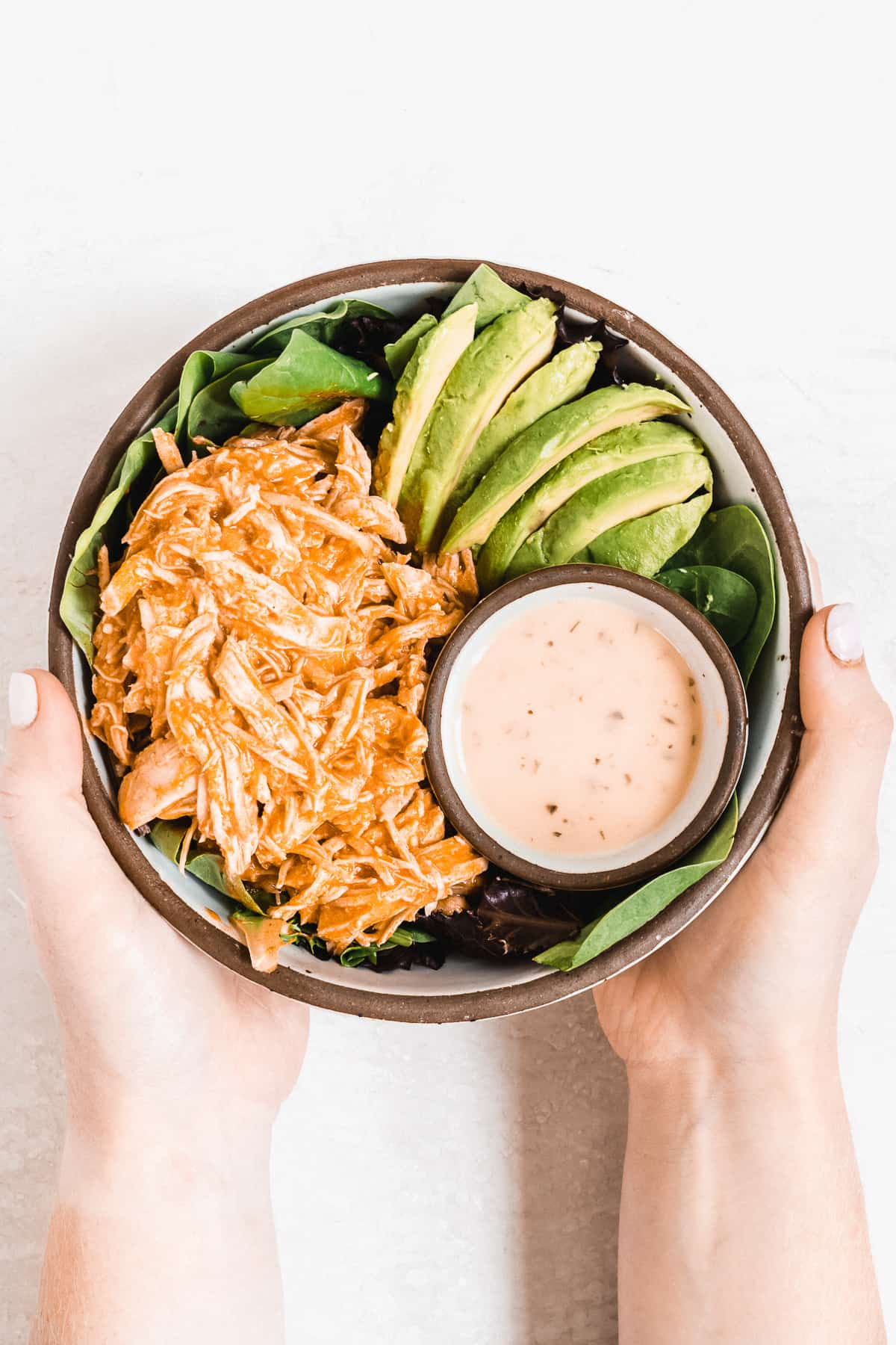 Hands holding bowl full of buffalo chicken, avocado slices, and dressing.