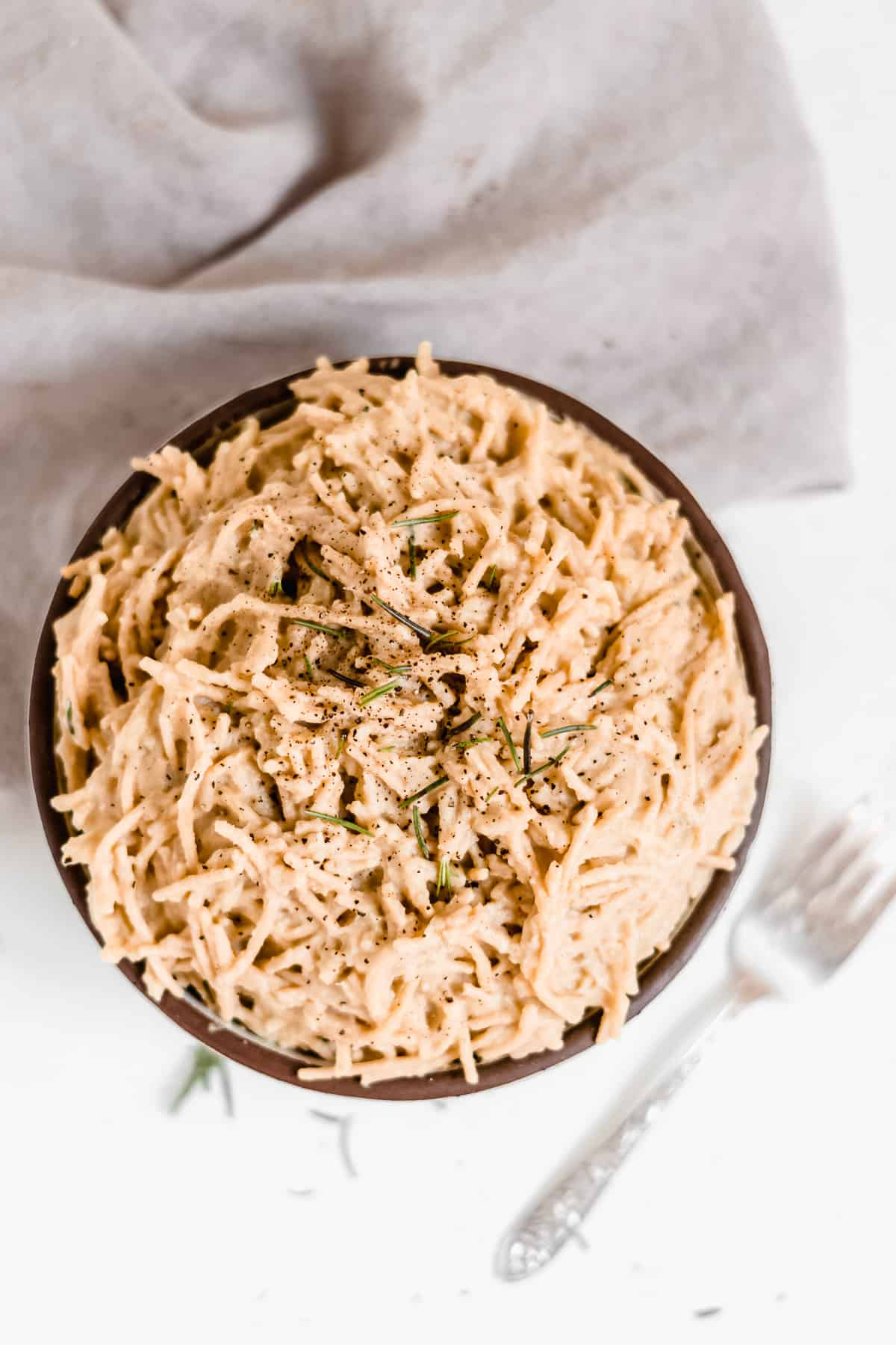 Overhead view of a big bowl of pasta with creamy white sauce and green herbs.