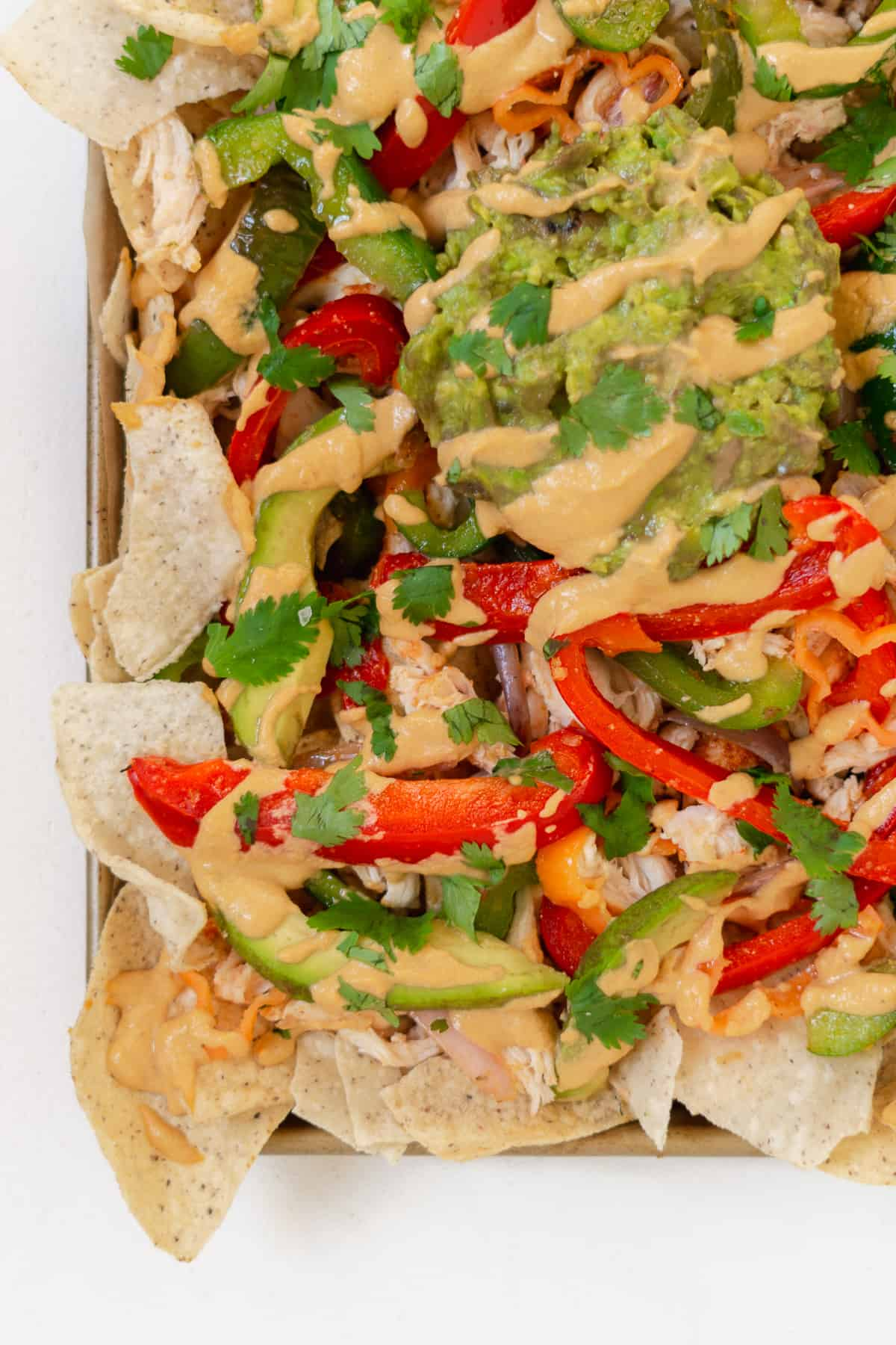 Corner of a pan filled with nachos topped with peppers.