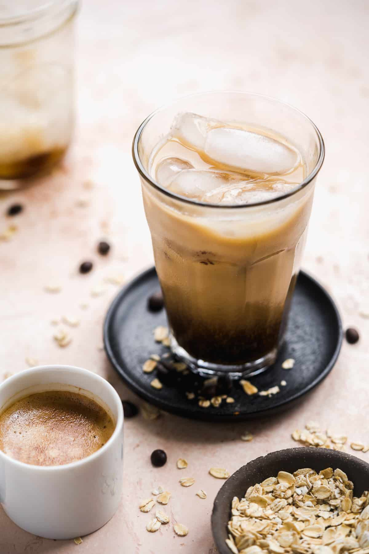 Glass filled with coffee and milk over ice sitting on a black coaster.