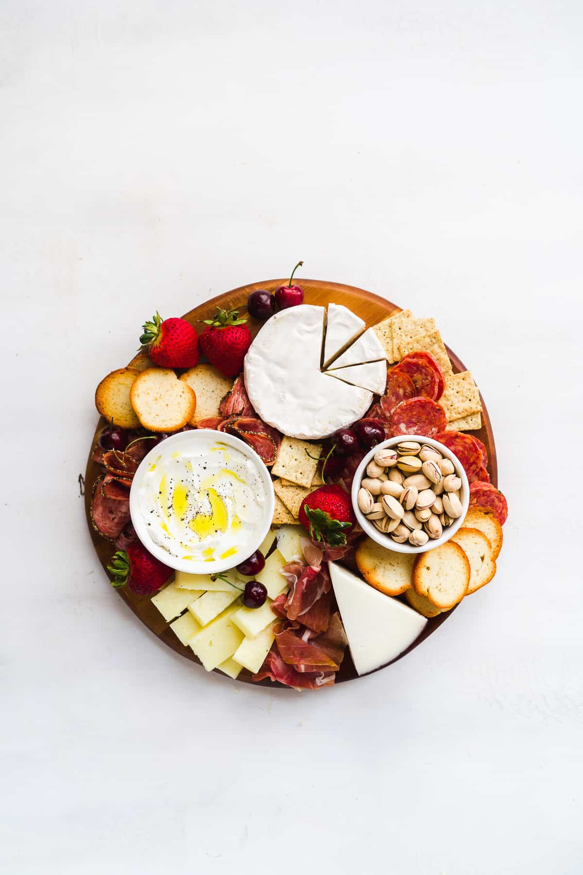 Charcuterie board with meats and bowls on a white surface.