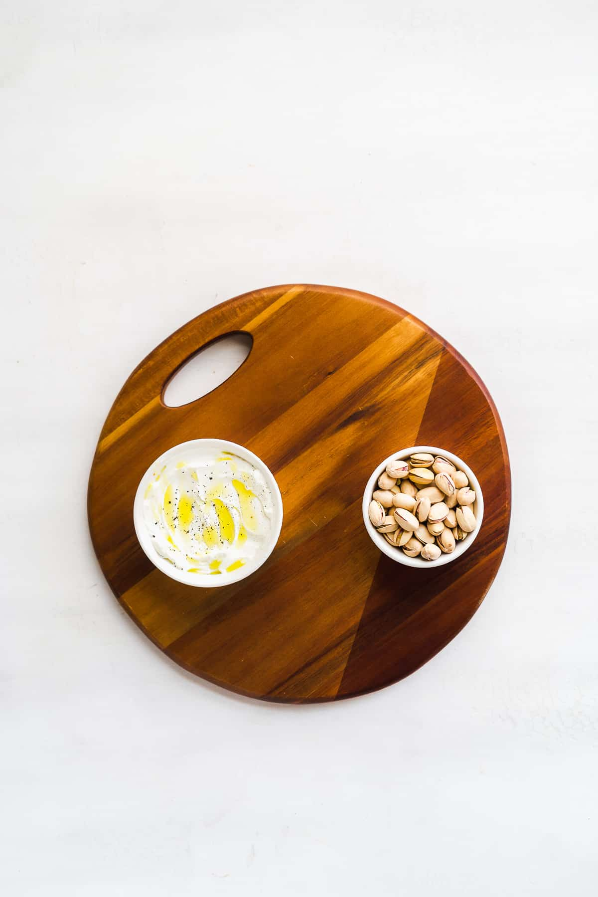 Wooden circular platter with two bowls on it on a white surface.