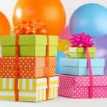 pile of colorful gifts surrounded by balloons