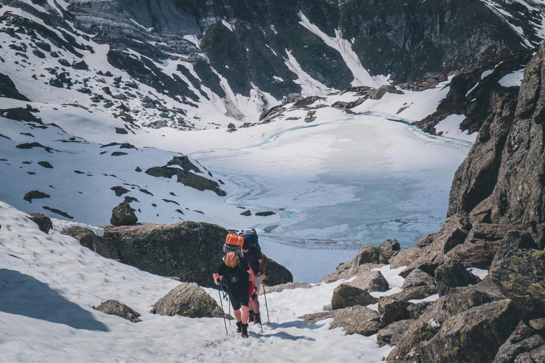 Aufstieg zum Passo di Leit mit zwei Wanderern und Bergsee im Hintergrund