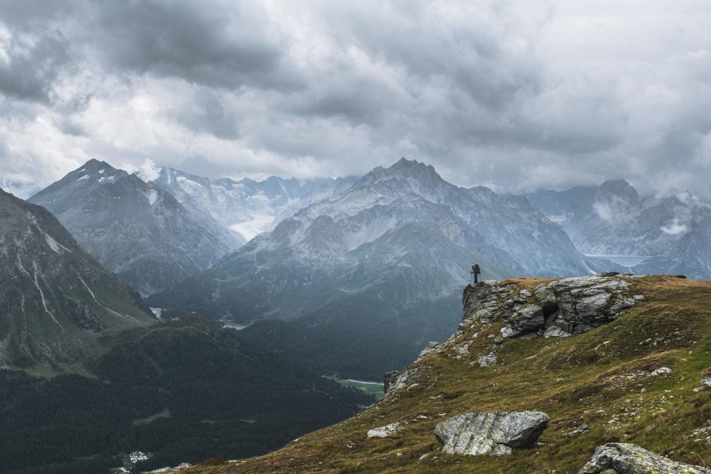 Wanderer steht an Felsvorsprung mit Blick auf die Berge