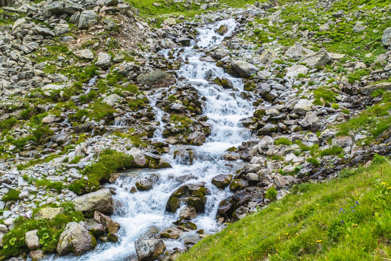 Bachlauf zwischen Steinen und Wiesen