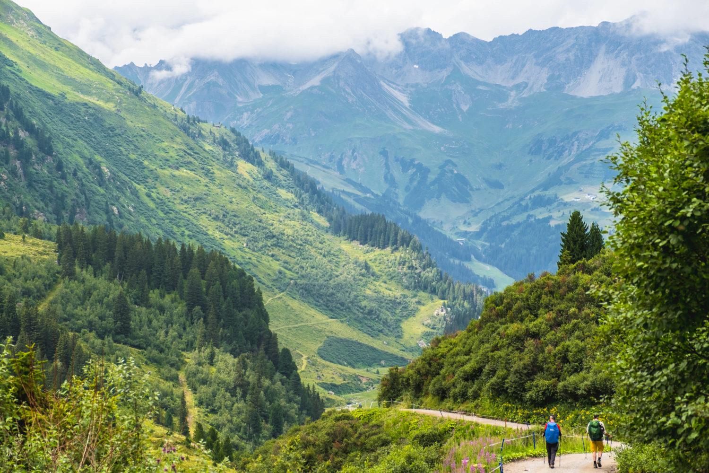 Zwei Wanderer auf einem Weg ins Tal zwischen grünen Berghängen