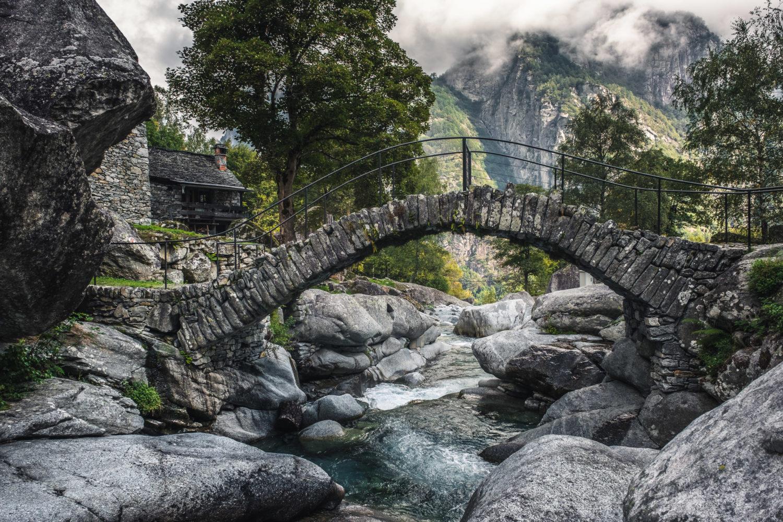 Steinbrücke im Val Bavona über einen Fluss mit Bergen im Hintergrund