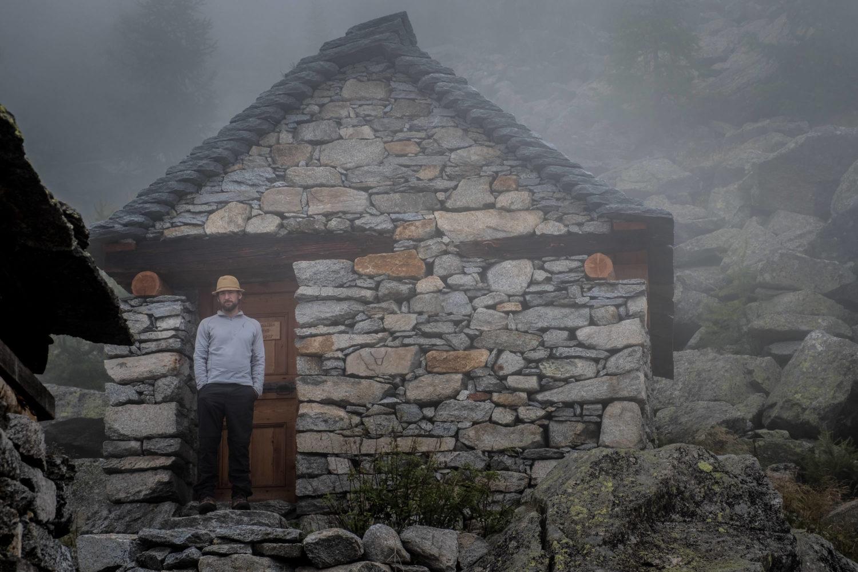 Mann mit Hut steht vor einer Steinhütte