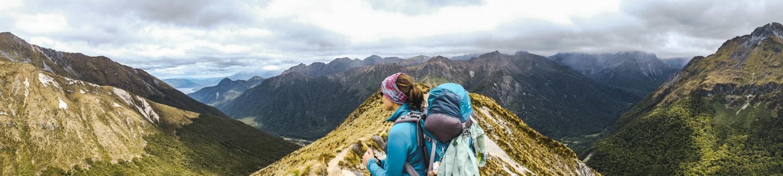 Eine Frau mit Rucksack sieht in die Ferne