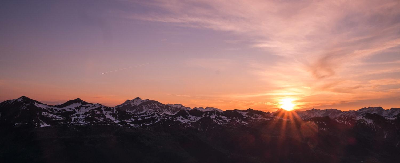 Sonnenaufgang vor schneebedeckter Bergkette am Passo di Leit
