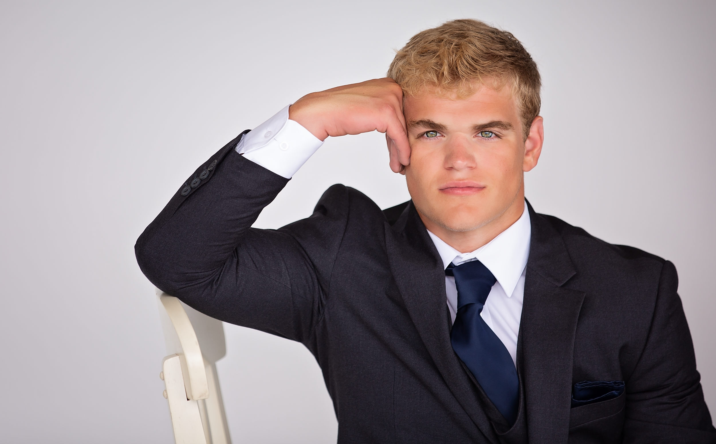 A striking senior photo headshot of a young man wearing a gray suit with a gray vest and navy blue tie with a white shirt sitting resting his head against his hand.