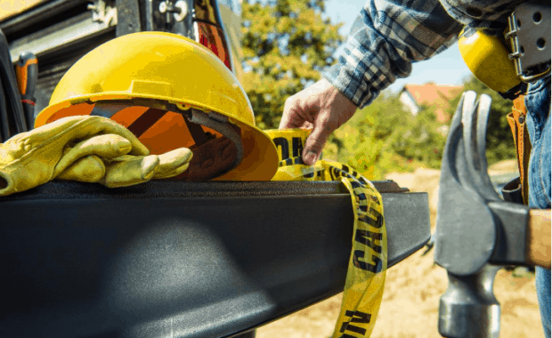 construction worker holding hammer avoids common construction injuries by grabbing hard hat, caution tape, and protective gear out of truck