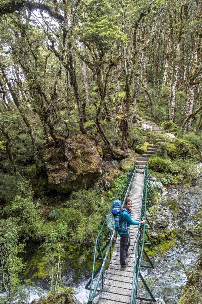 Eine Frau geht über eine Brücke im Wald