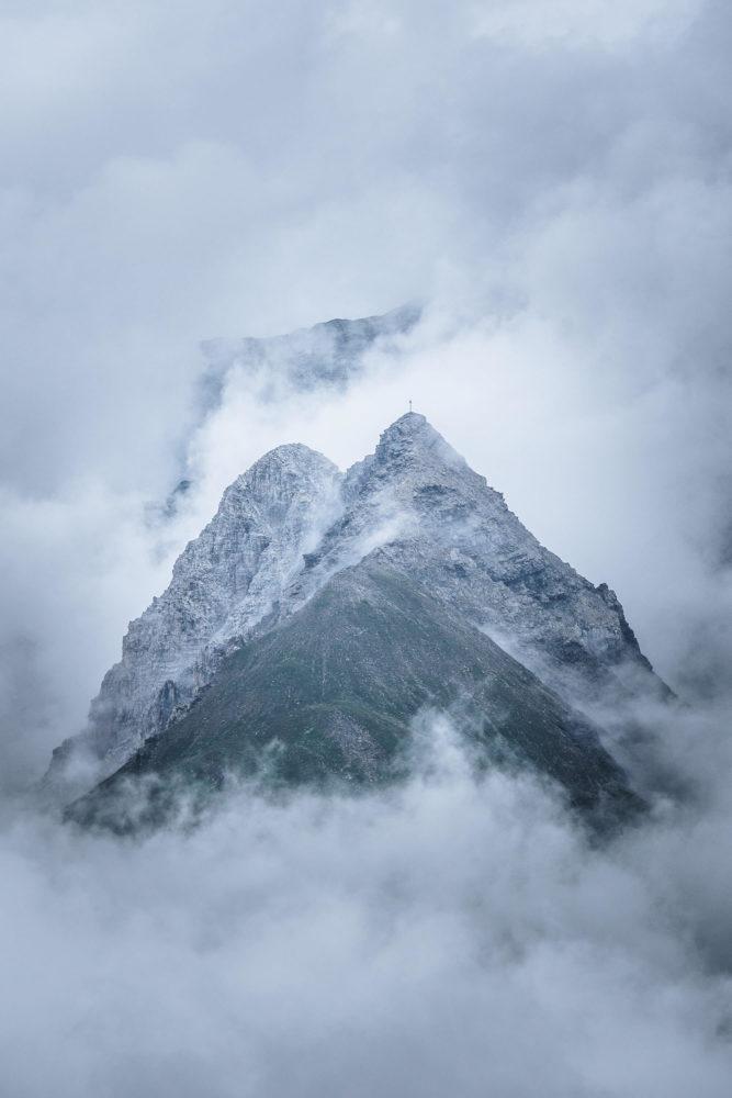 Gipfelspitze zwischen den Wolken in den Alpen bei Bivio