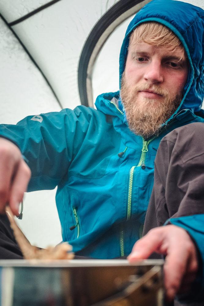 Wanderer sitzt im Zelt und kocht auf einem Gaskocher
