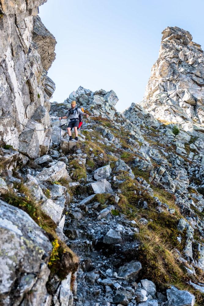Christopher Püschel steigt einen steilen felsigen Hang hinab