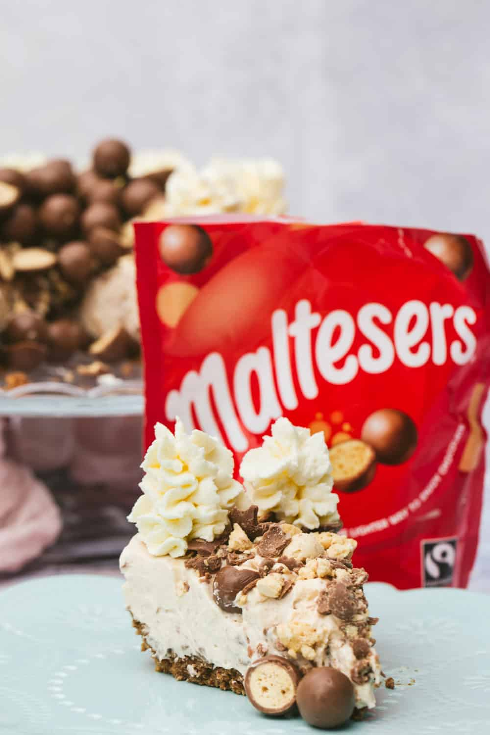 A slice of Malteser cheesecake in the foreground and a bag of red Maltesers in the background