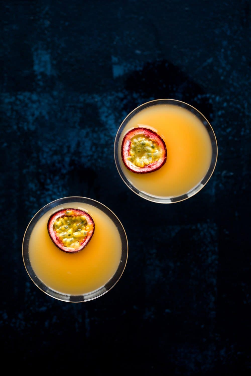 Overhead view of two pornstar martini cocktails with passion fruit slices floating on top.