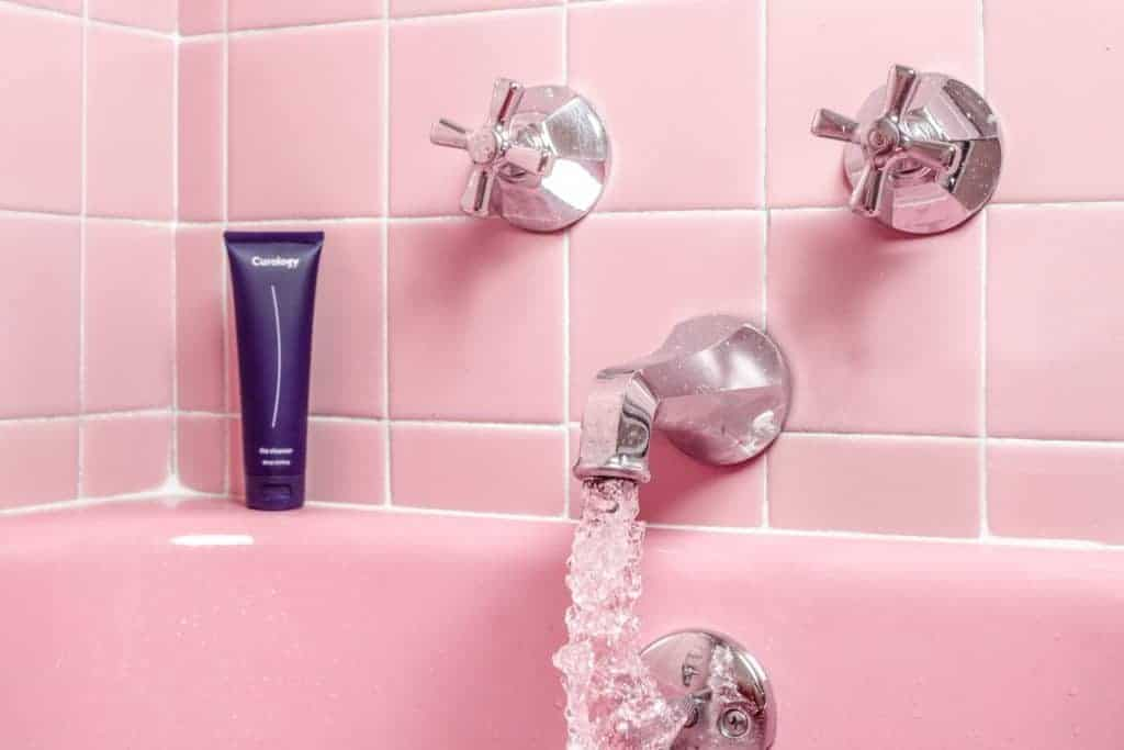 pink bath tub and tiles with a purple body wash tube