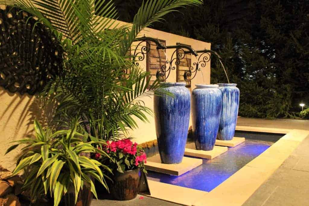 Fountains fill ornate vessels against a stucco wall with bluestone patio and limestone accents.