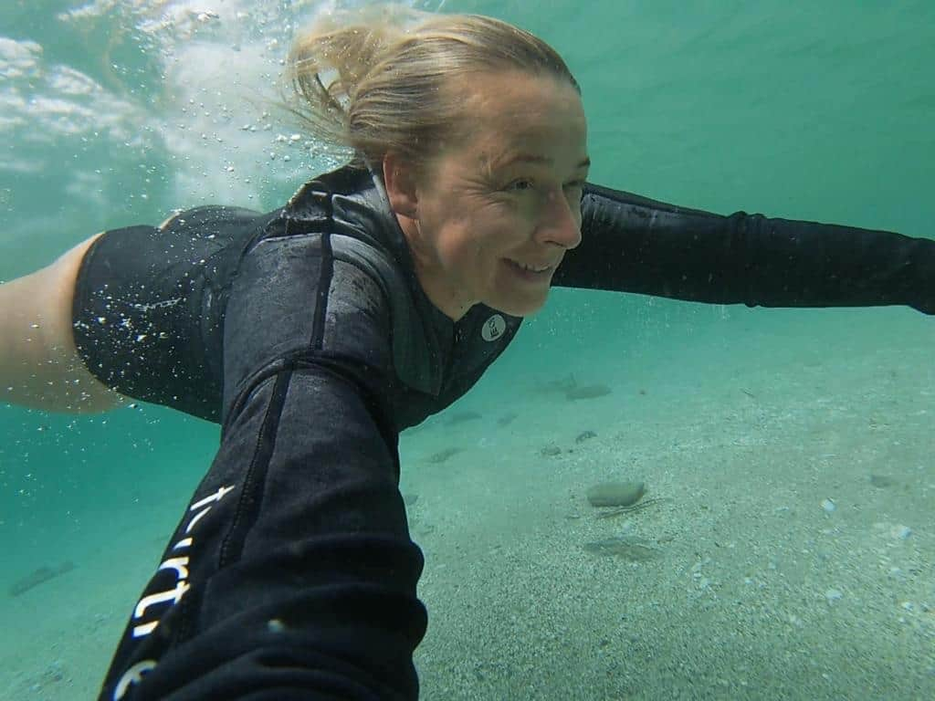Gemma in neoprene sea swimming underwater