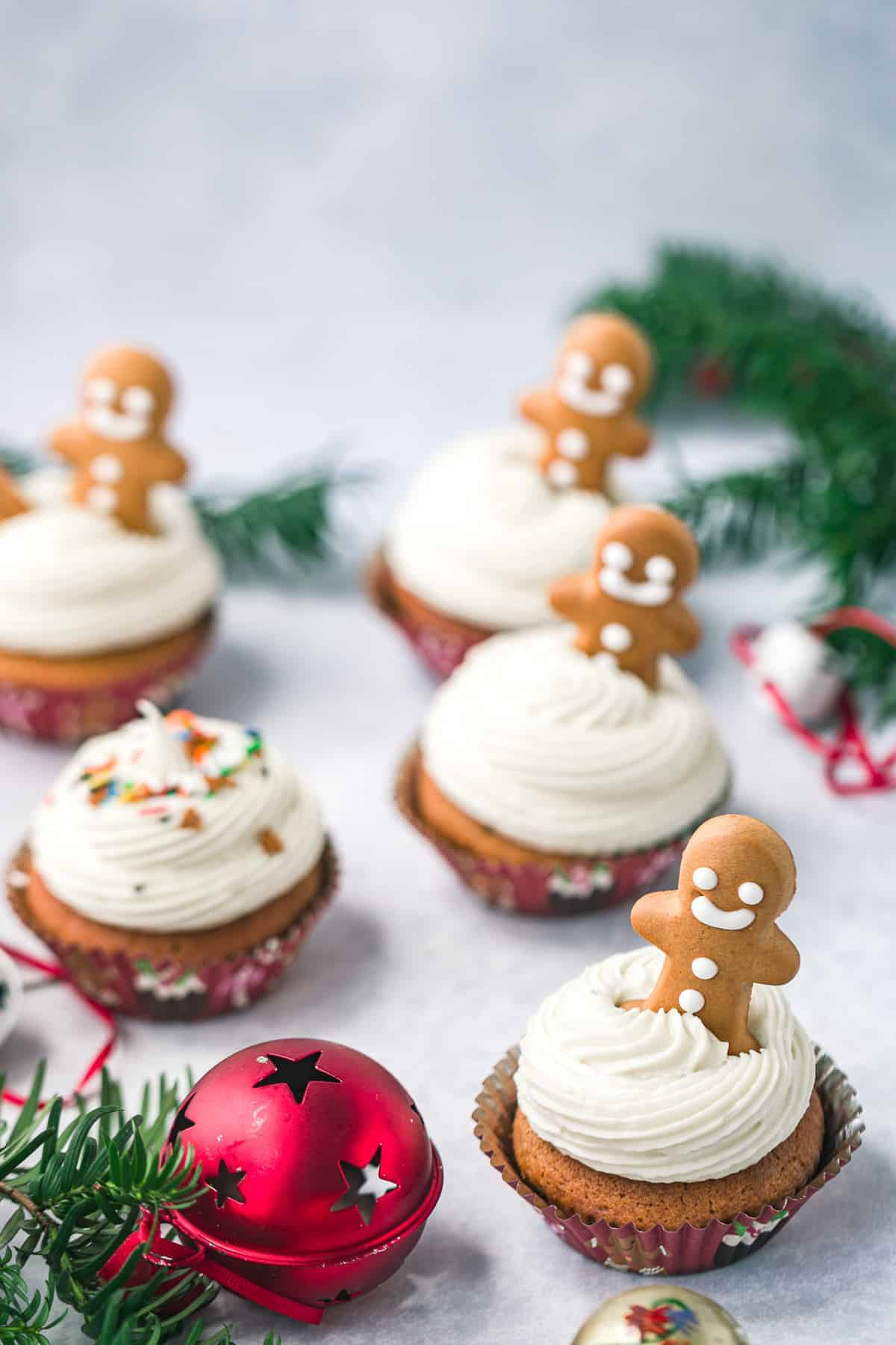 5 gingerbread cupcakes topped with cream cheese frosting and a mini gingerbread man.
