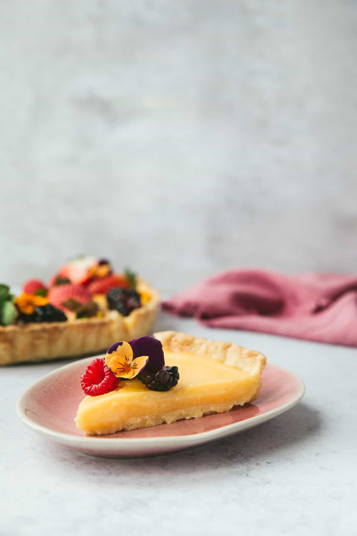 A slice of lemon tart on a small pink plate.