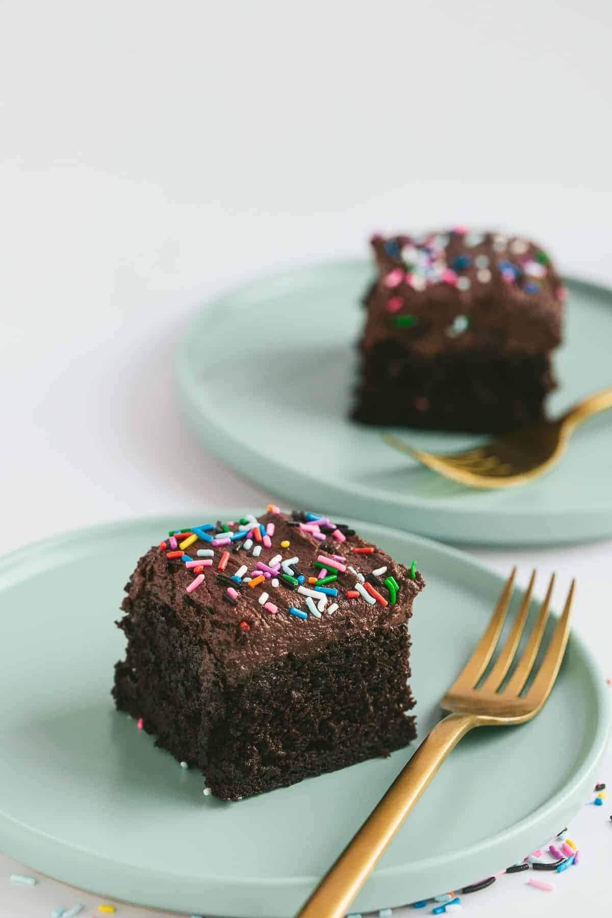 A piece of old school chocolate sprinkle cake on a green cake.