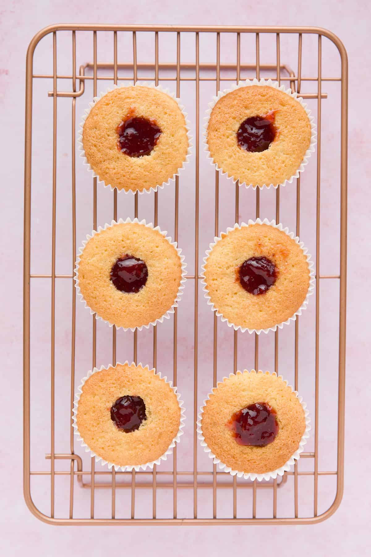 Step by step image showing strawberry jam that has been put into the centre of cupcakes.